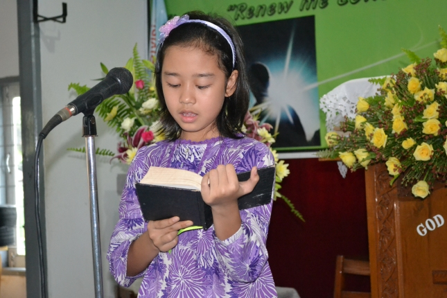 Young girl helping out during song service time